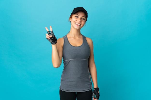 Teenager-sportmädchen auf blau lächelnd und siegeszeichen zeigend