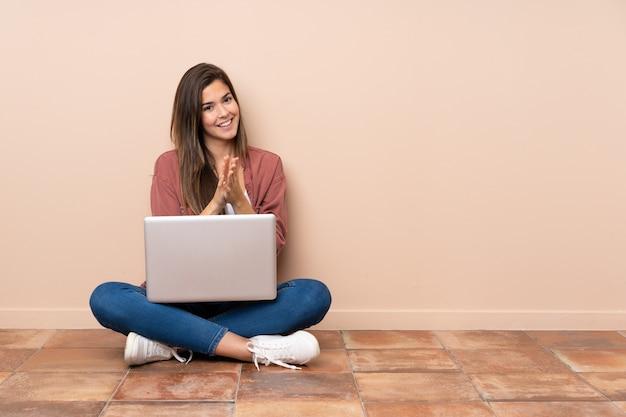 Teenager-student, der auf dem boden mit einem laptop sitzt, der nach der präsentation in einer konferenz applaudiert