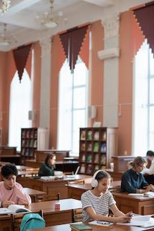 Teenager-student, der im smartphone durch schreibtisch in der hochschulbibliothek unter anderen lernenden rollt, die für seminar vorbereiten