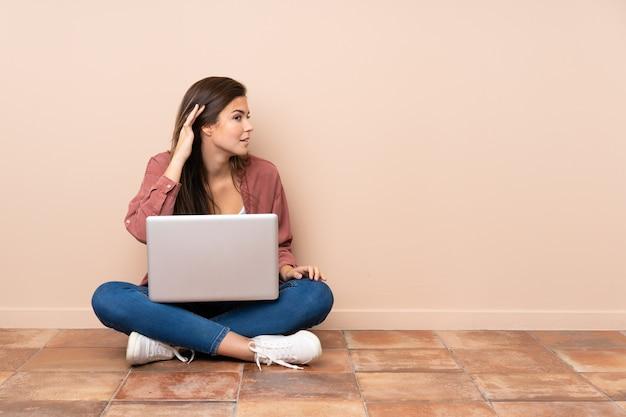 Teenager-studentenmädchen, das auf dem boden mit einem laptop sitzt, der etwas hört, indem man hand auf das ohr legt