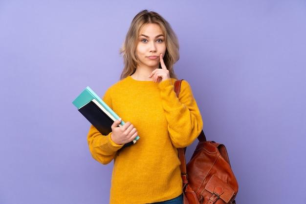 Teenager-studentenmädchen lokalisiert auf lila und schauende front