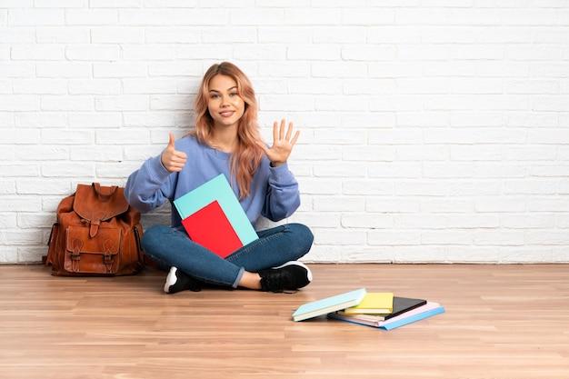 Teenager-studentin mit rosa haaren, die auf dem boden drinnen sitzen und sechs mit den fingern zählen