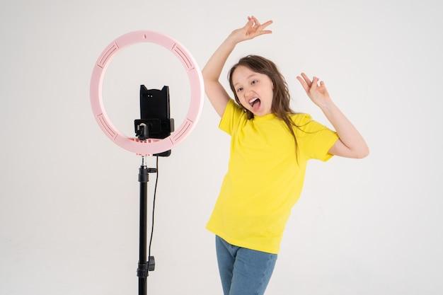 Teenager tanzt und dreht ein video. das telefon ist auf einem stativ montiert und die ringlampe leuchtet.