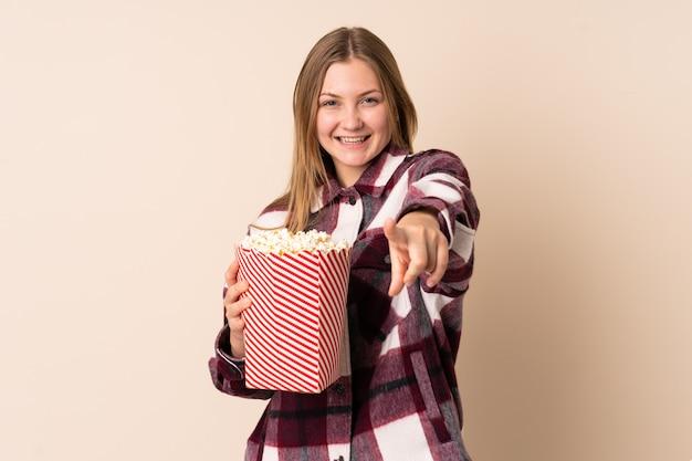 Teenager ukrainische frau lokalisiert auf beigem raum, der einen großen eimer popcorns hält, während er nach vorne zeigt