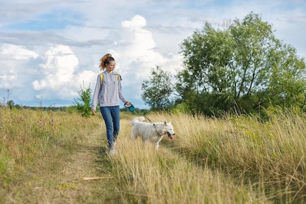 Teenager und husky gehen im freien
