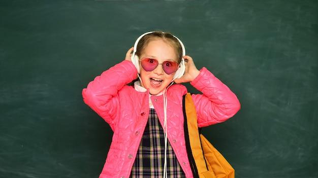 Teenager-younf-schulmädchen mit brillenrucksack und kopfhörern.