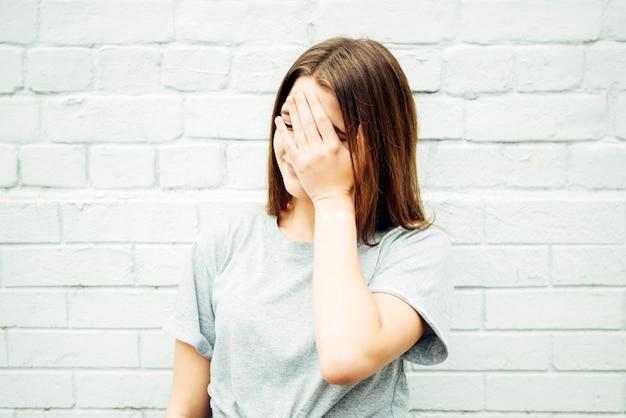 Teenager zeigt gesichtspalmengeste auf der straße.
