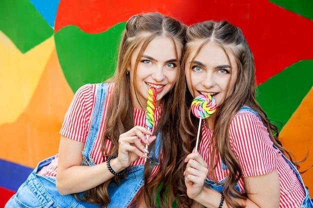 Teenager-zwillingsschwestern in bunten kleidern mit lutschern auf bunter wand