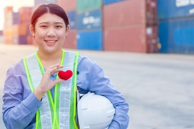 Teenagerarbeit des mädchens im frachtcontainerversandhafen, der mit herz und gutem service-verstand-konzept arbeitet.