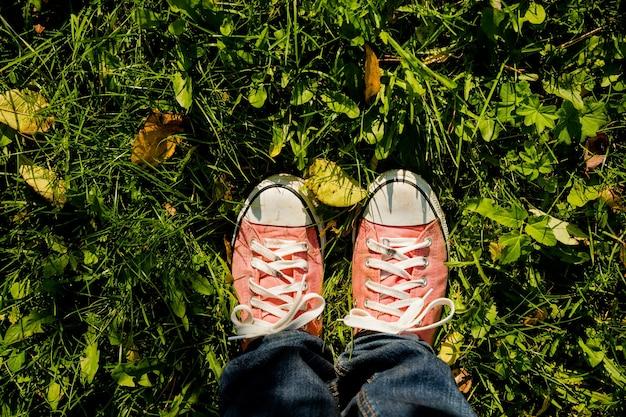 Teenagerbeine in textilmaterialstiefeln, die mit gefallenen blättern auf dem boden stehen, draufsicht. konzept zum saisonwechsel. herbstmode-stil. blue jeans.hipster pinke schuhe an einem sonnigen tag