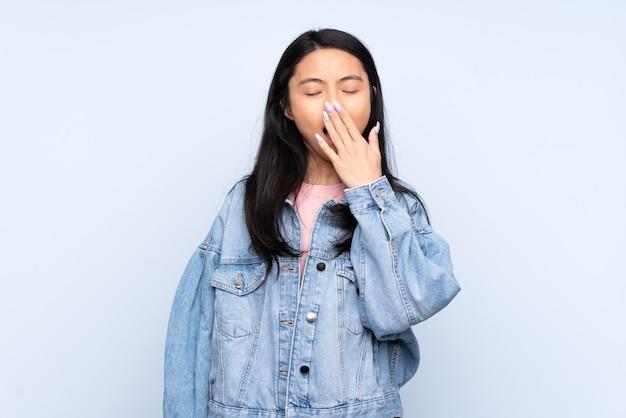 Teenagerfrau isoliert auf blauem gähnen und weit offenem mund mit hand bedeckend