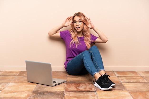 Teenagerfrau mit einem laptop, der auf dem boden drinnen mit überraschungsausdruck sitzt