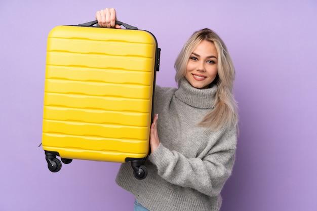 Teenagerfrau über isolierte lila wand im urlaub mit reisekoffer