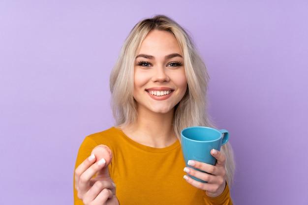 Teenagerfrau über isolierter lila wand, die bunte französische macarons und eine tasse milch hält