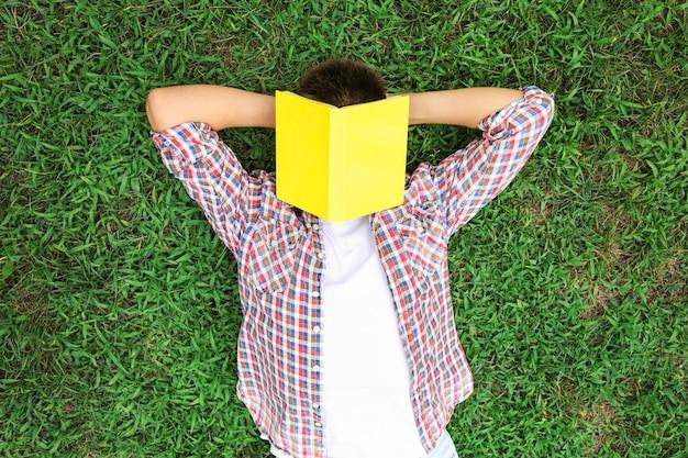Teenagerjunge mit buch, das auf grünem gras liegt