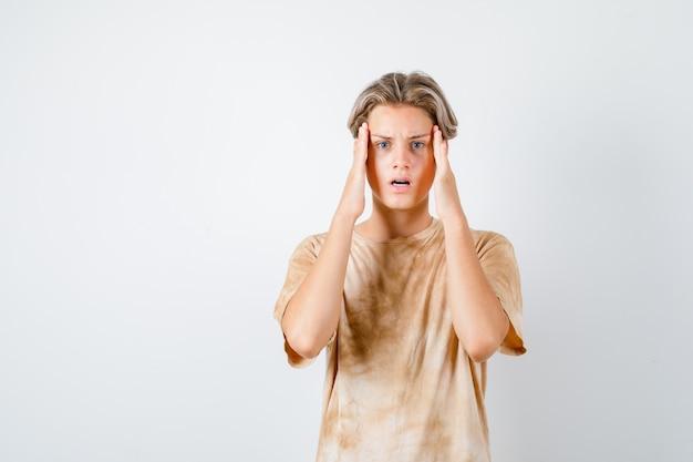 Teenagerjunge reibt tempel im t-shirt und sieht frustriert aus, vorderansicht.