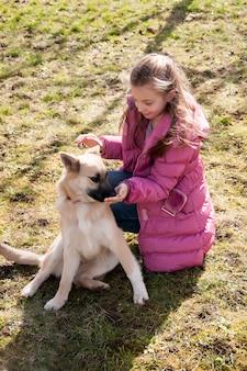 Teeneger-mädchen, das draußen mit ihrem hund spielt