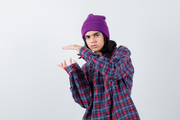 Teenie-frau, die die hand ausdehnt, während sie etwas in einem karierten hemd hält, das süß aussieht