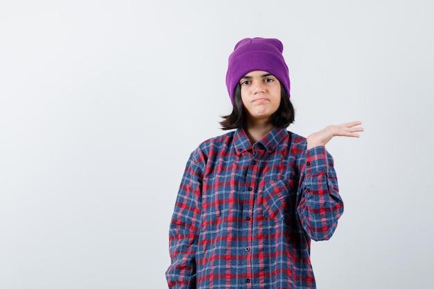 Teenie-frau, die etwas in kariertem hemd und mütze hält und vorsichtig aussieht