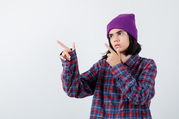 Teenie-frau, die mit den zeigefingern in kariertem hemd und mütze nach links zeigt, sieht ernst aus