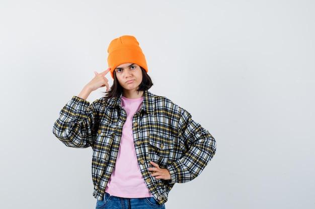 Teenie-frau in t-shirt-jacke-mütze, die den finger an den schläfen hält und ernst aussieht