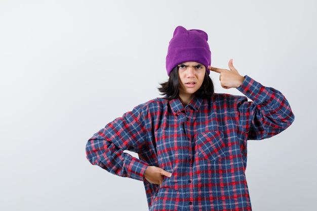 Teenie-frau mit dem finger an den schläfen in kariertem hemd und mütze, die ernst aussieht