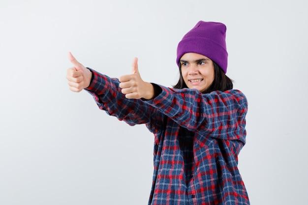 Teenie-frau mit doppeltem daumen nach oben in kariertem hemd und mütze, die süß aussieht