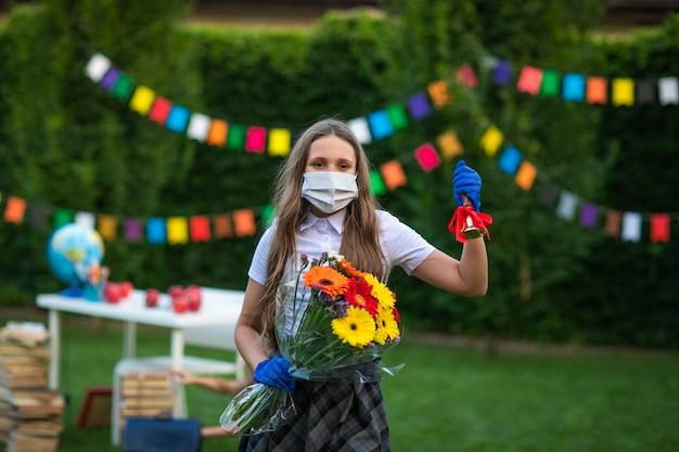 Teenie-mädchen an der medizinischen maske und an den handschuhen, die blumenstrauß und schulglocke halten