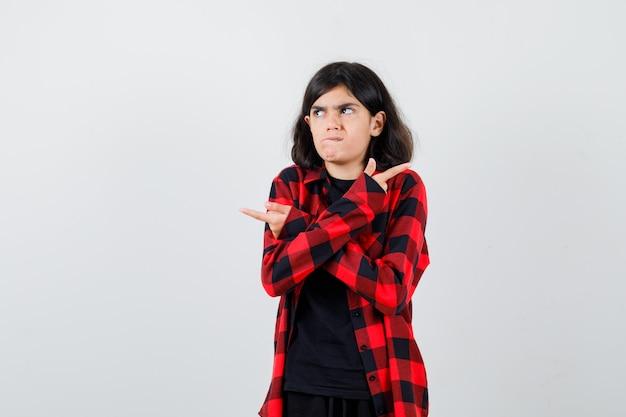 Teenie-mädchen, das auf beide seiten in t-shirt, kariertem hemd zeigt und unentschlossen aussieht. vorderansicht.