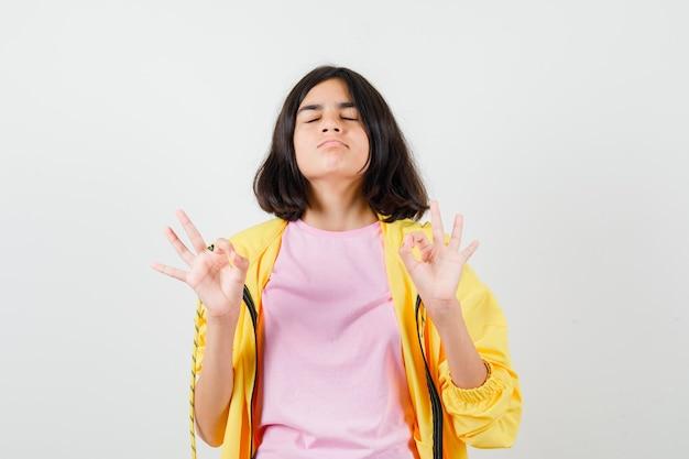 Teenie-mädchen, das eine ok geste mit geschlossenen augen in gelbem trainingsanzug, t-shirt zeigt und müde aussieht, vorderansicht.
