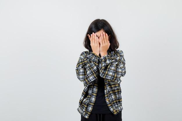 Teenie-mädchen, das gesicht mit den händen in lässigem hemd bedeckt und genervt aussieht, vorderansicht.