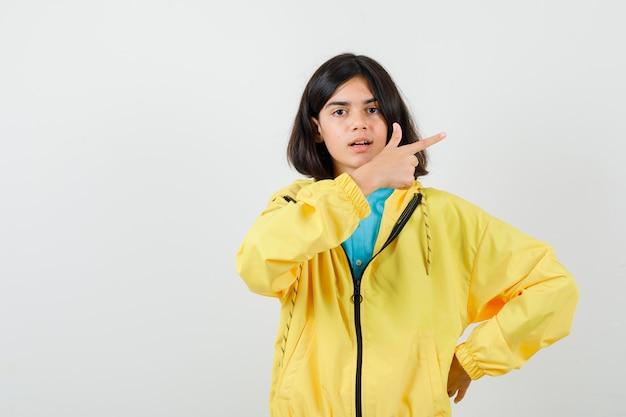 Teenie-mädchen, das nach rechts zeigt, während es die hand auf der taille im hemd, in der gelben jacke hält und trostlos aussieht. vorderansicht.