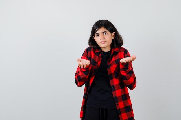 Teenie-mädchen im freizeithemd, das hilflose geste zeigt und verwirrt aussieht, vorderansicht.