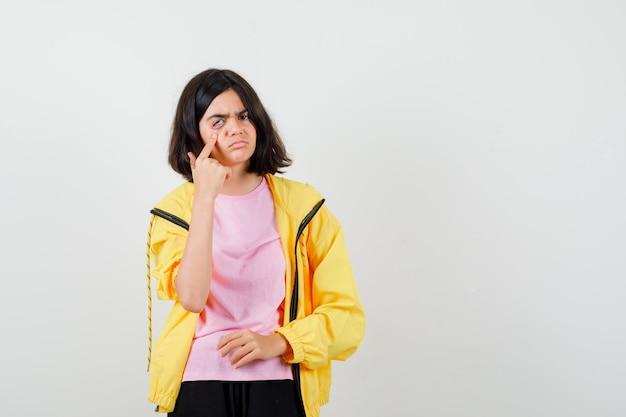 Teenie-mädchen im gelben trainingsanzug, t-shirt, das das auge mit dem finger nach unten zieht und traurig aussieht, vorderansicht.