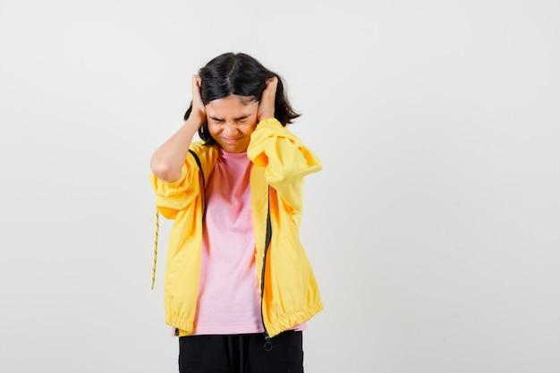 Teenie-mädchen im gelben trainingsanzug, t-shirt, das den kopf mit den händen hält und aggressiv aussieht, vorderansicht.