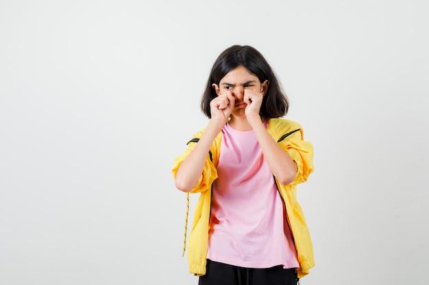 Teenie-mädchen im gelben trainingsanzug, t-shirt, das die augen mit fäusten reibt, während es weint und mürrisch aussieht, vorderansicht.