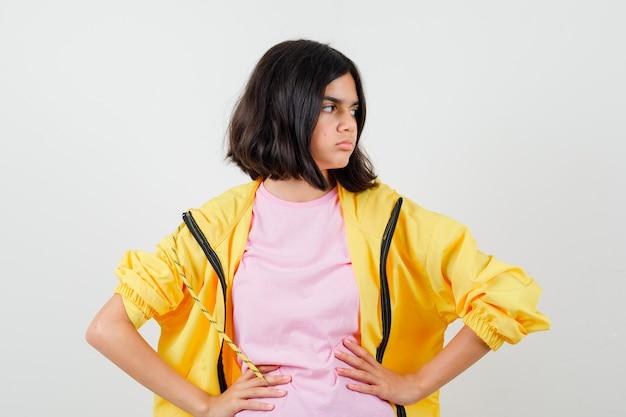 Teenie-mädchen im gelben trainingsanzug, t-shirt, das die hände an der taille hält, zur seite schaut und verwirrt aussieht, vorderansicht.