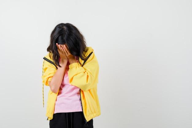 Teenie-mädchen im gelben trainingsanzug, t-shirt, das gesicht mit den händen bedeckt und verärgert aussieht, vorderansicht.