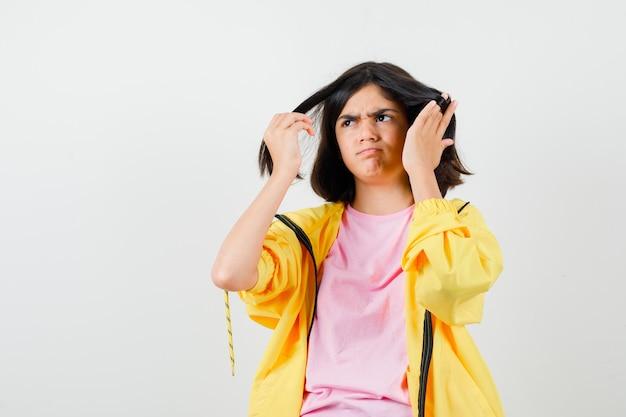 Teenie-mädchen im gelben trainingsanzug, t-shirt, das händchen im haar hält und düster aussieht, vorderansicht.