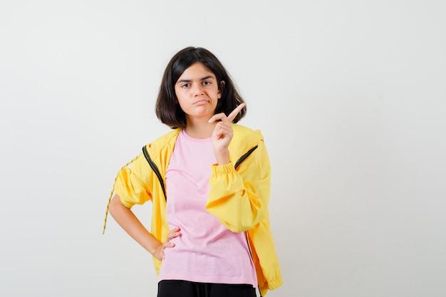 Teenie-mädchen im gelben trainingsanzug, t-shirt, das mit dem finger nach oben zeigt und düster aussieht, vorderansicht.