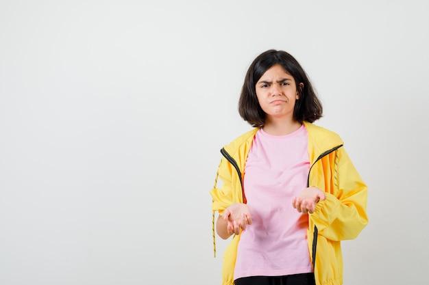 Teenie-mädchen im gelben trainingsanzug, t-shirt, das mit dummer frage unzufrieden ist und düster aussieht, vorderansicht.