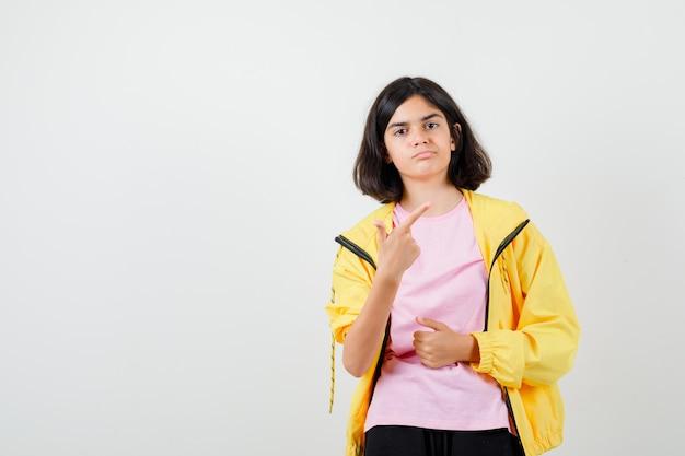 Teenie-mädchen im gelben trainingsanzug, t-shirt nach oben und unzufrieden aussehend, vorderansicht.