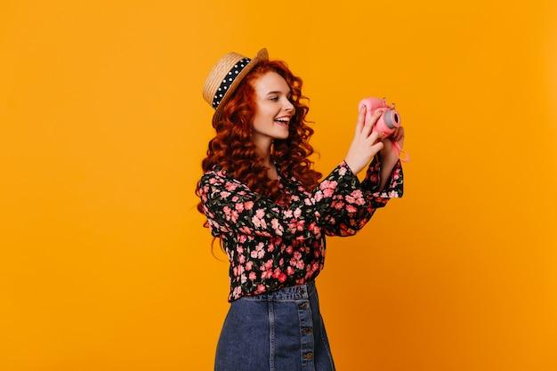 Teenie-mädchen im jeansrock und in der stilvollen bluse macht glücklich foto, das mini-kamera auf orange raum hält.
