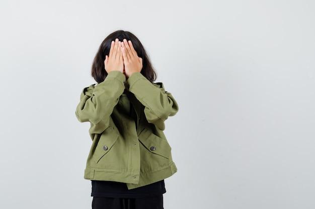 Teenie-mädchen im t-shirt, grüne jacke, die das gesicht mit den händen bedeckt und traurig aussieht, vorderansicht.