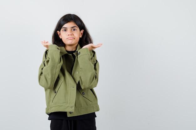 Teenie-mädchen im t-shirt, grüne jacke, die zweifelsgeste zeigt und unentschlossen aussieht, vorderansicht.