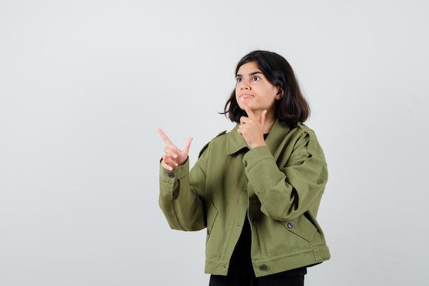 Teenie-mädchen im t-shirt, jacke, die weg zeigt und fokussiert aussieht, vorderansicht.