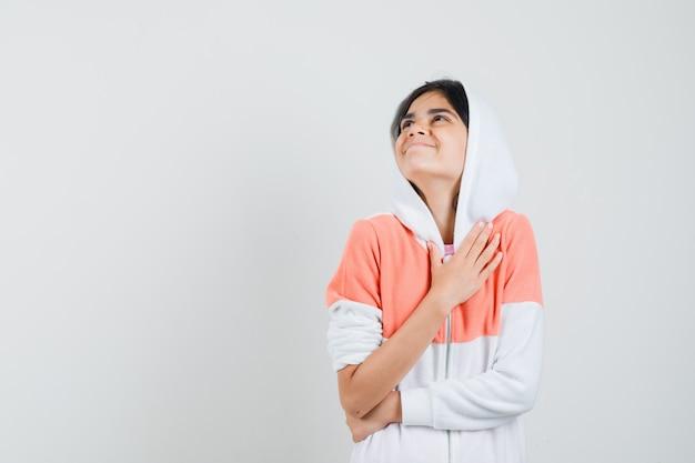 Teenie-mädchen in der weißen jacke, die hand auf ihrer brust hält und dankbar schaut.