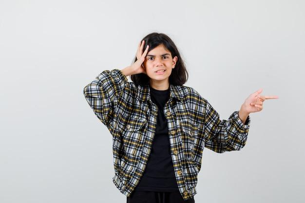 Teenie-mädchen in freizeithemd, das hand auf den kopf hält, nach rechts zeigt und verwirrt aussieht, vorderansicht.