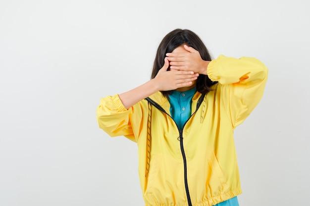 Teenie-mädchen in gelber jacke, die das gesicht mit den händen bedeckt und verängstigt aussieht, vorderansicht.