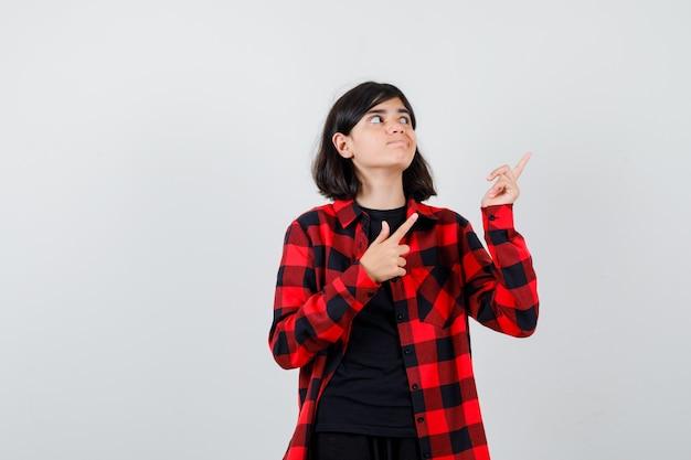 Teenie-mädchen in lässigem hemd, das auf die obere rechte ecke zeigt, wegschaut und zögerlich aussieht, vorderansicht.